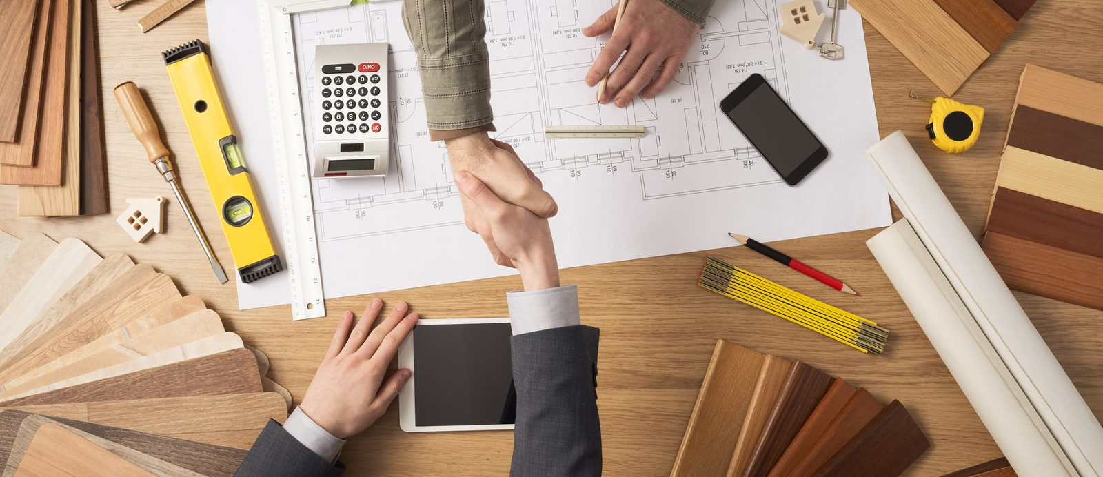 Architect and customer businessman shaking hands top view desktop with building project tools and wood swatches on background